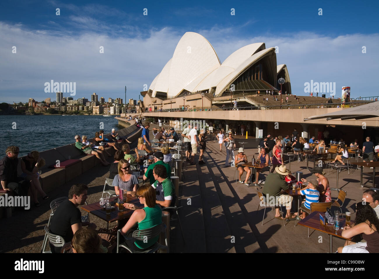 People enjoying waterfront drinks at the Opera Bar, at the foot of the Opera House. Sydney, New South Wales, Australia - Stock Image