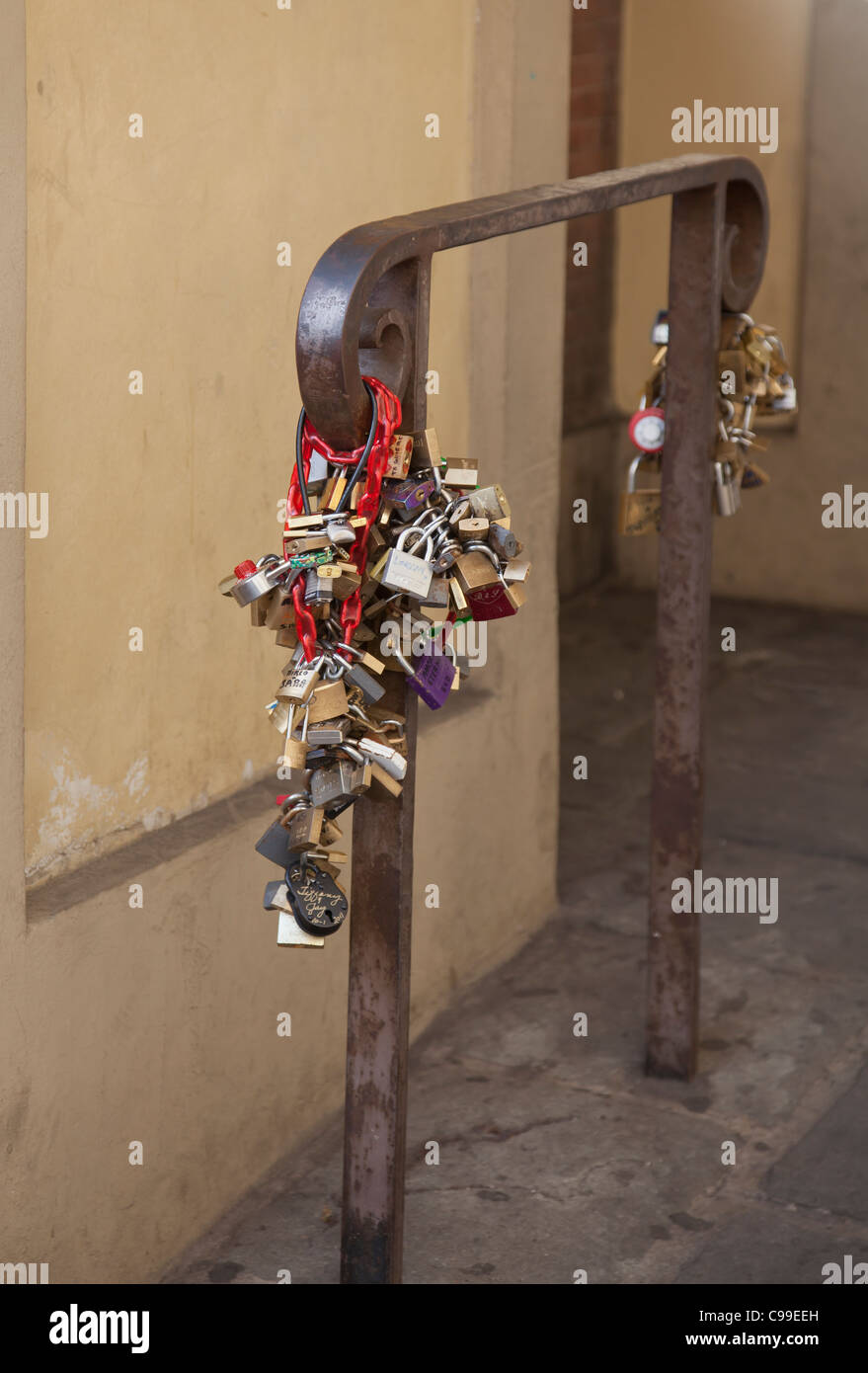 Padlocks attached to a rail at Ponte Vecchio in Florence as a romantic symbol of commitment - Stock Image