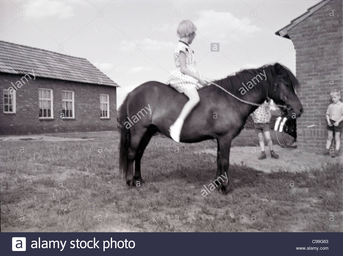 a young girl sitting on the back of a pony with other children looking on Holland - Stock Image