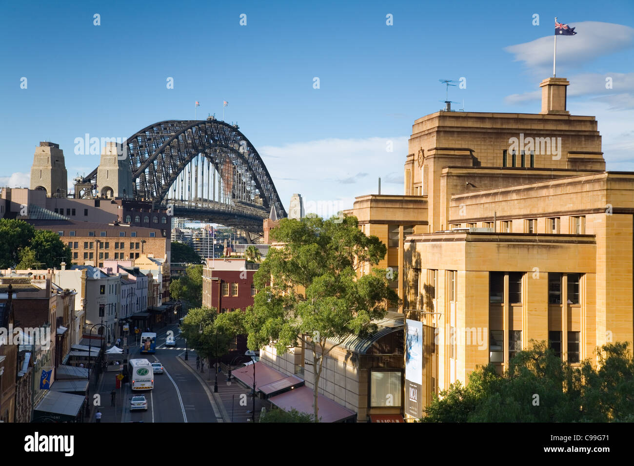 View along historic George Street in The Rocks district, with Sydney Harbour Bridge beyond.  Sydney, New South Wales, - Stock Image