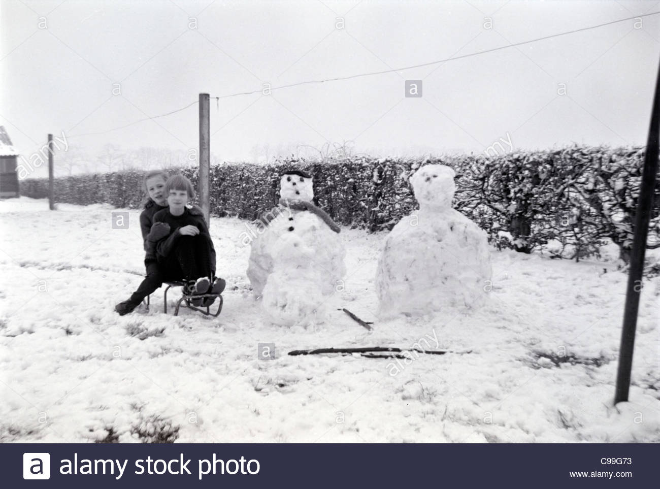 girls posing with their snowman 1960s - Stock Image
