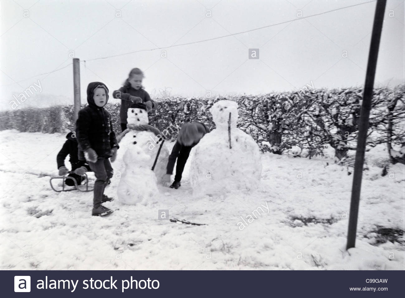 children making snowman 1960s - Stock Image