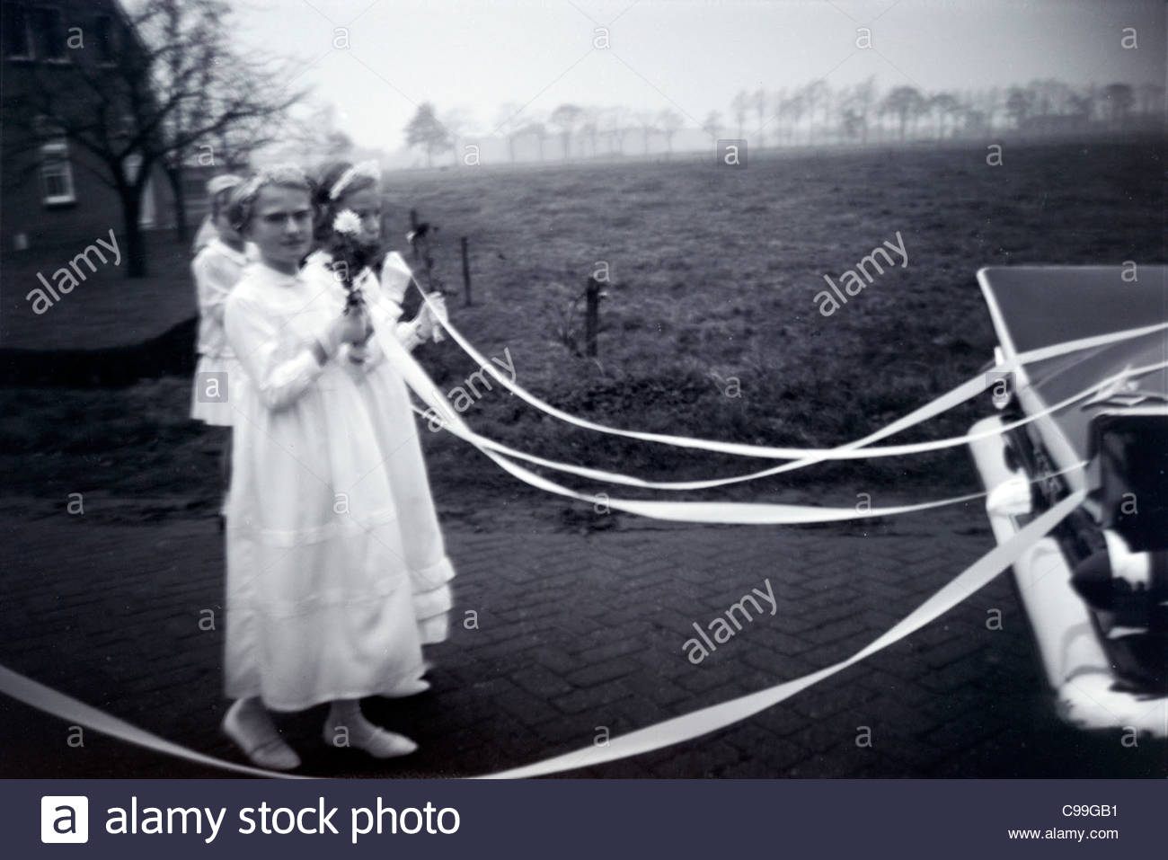 Brides maids following the wedding car 1960s Holland - Stock Image