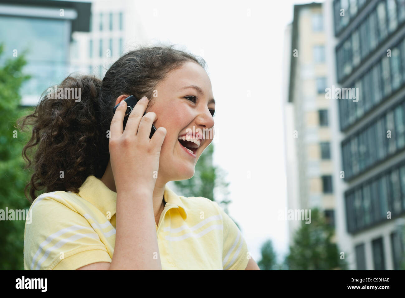 Germany, Berlin, Teenage girl using cell phone in city, laughing Stock Photo