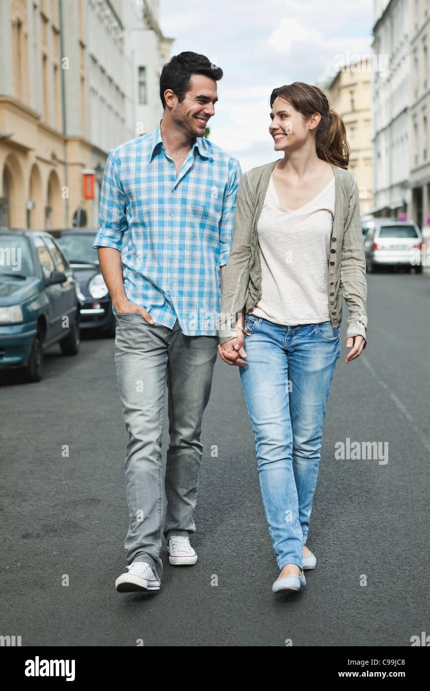 Germany, Berlin, Couple walking hand in hand through city street Stock Photo