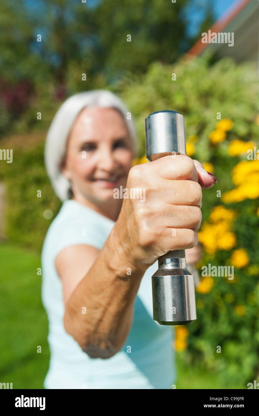 Germany, Bavaria, Senior woman doing exercise with dumbbell - Stock Image