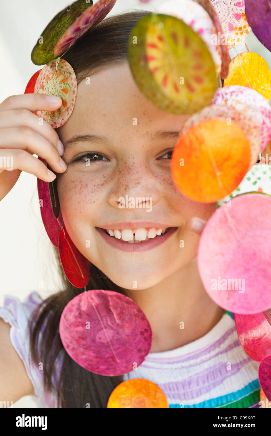 Germany, Bavaria, Girl looking through decorative sea shells wind chime - Stock Image