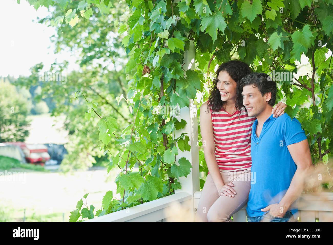 Germany, Bavaria, Couple in garden, smiling - Stock Image