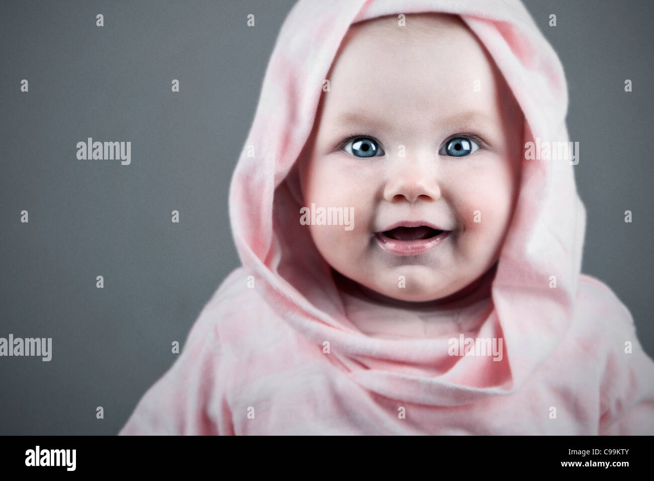 Shot of a Beautiful Baby Girl in Pink Hooded Top - Stock Image
