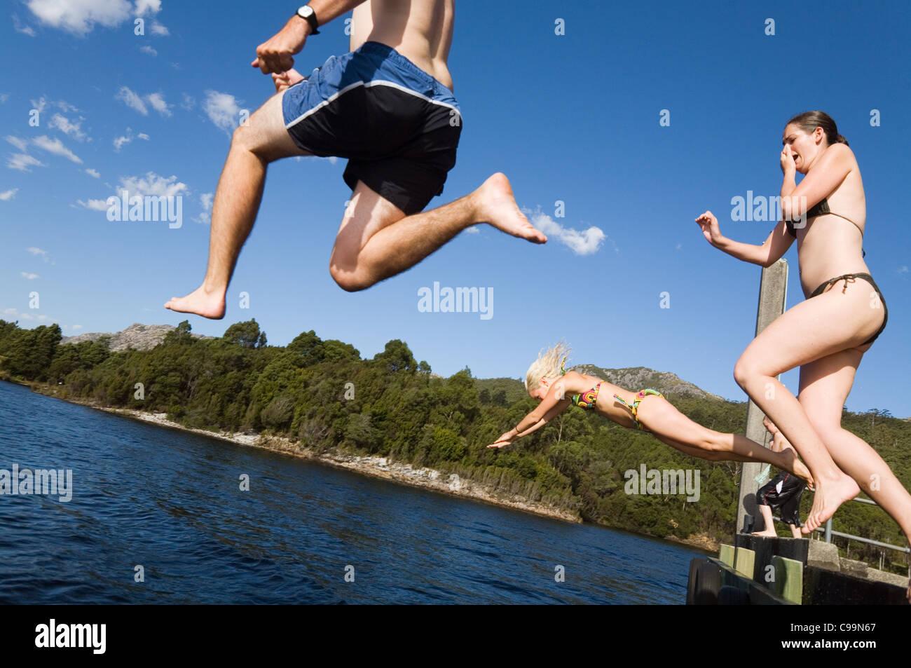 A group jumping off a pier into a lake. Lake Rosebery, Tullah, Tasmania, Australia Stock Photo