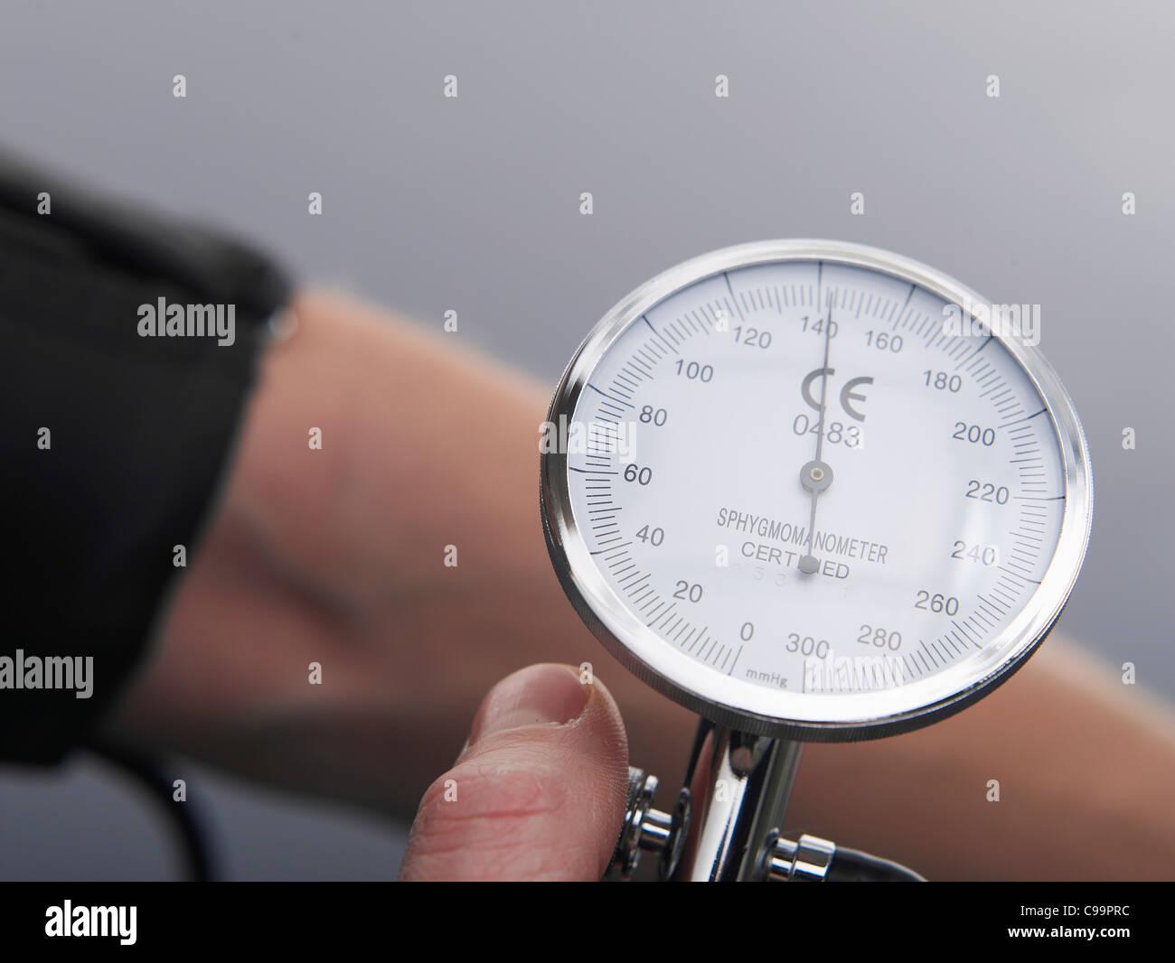 Human hand holding blood pressure gauge, close up - Stock Image