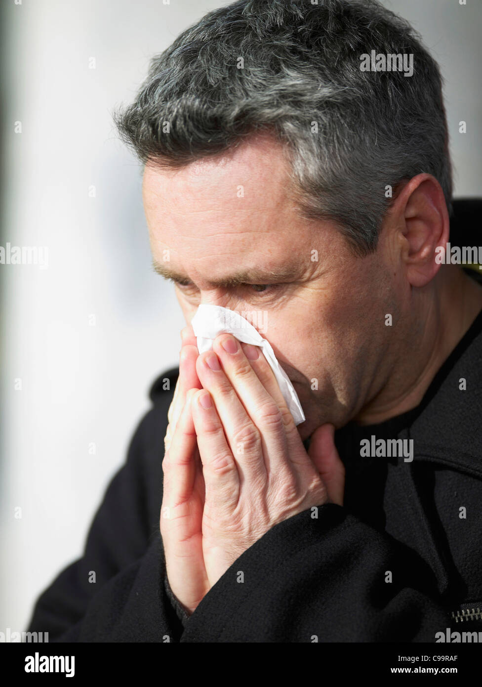 Germany, Hamburg, Mature man blowing nose with tissue, close-up - Stock Image
