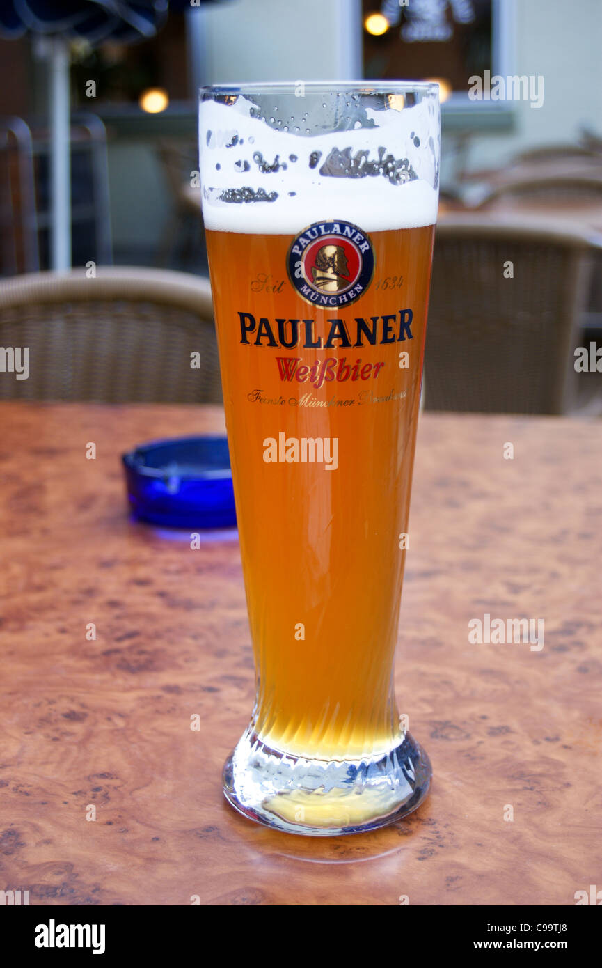 A printed glass of Paulaner weissbier wheat beer in a bar in Speyer, Rheinland-Pfalz, Germany pub table drinks glasses - Stock Image