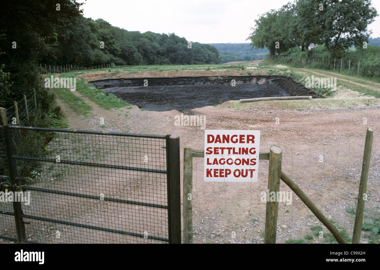 A settling lagoon for slurry to prevent pollution but securely fenced - Stock Image