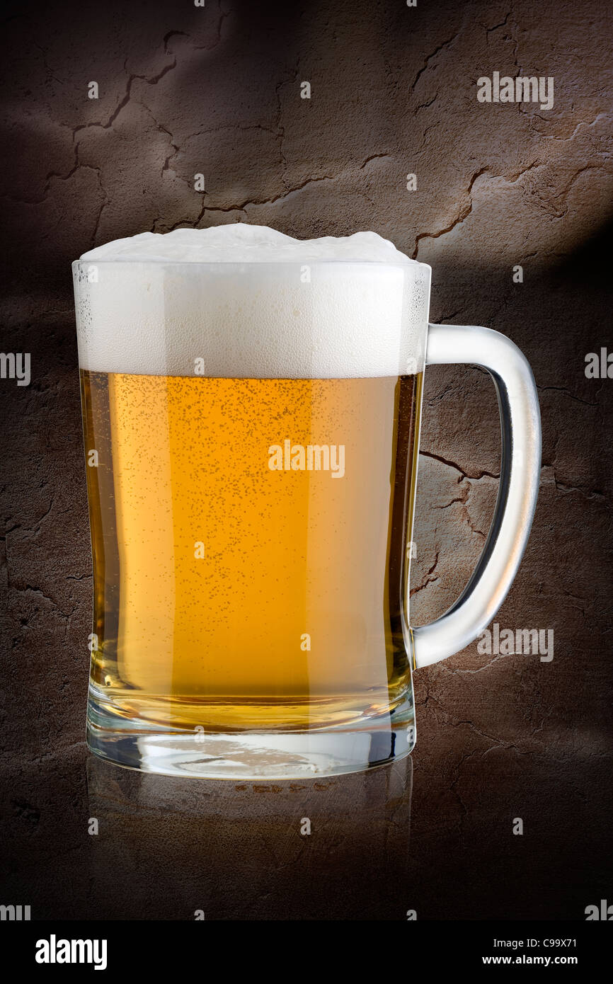 Stein of Lager pilsner against a stone background - Stock Image