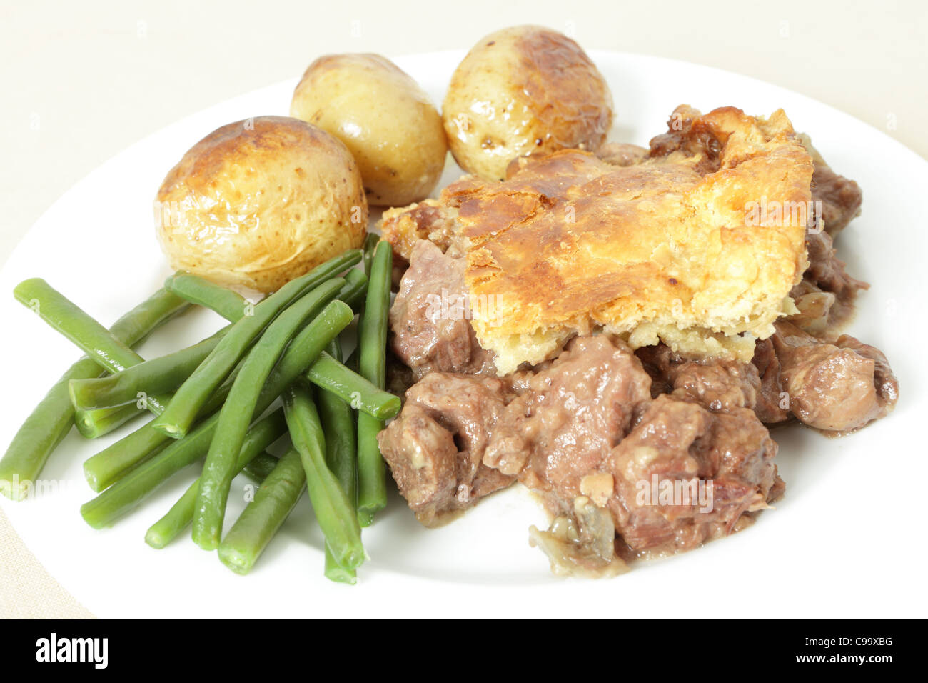 A traditional, home-made steak and kidney pie served with oven roasted potatoes and haricot beans. - Stock Image