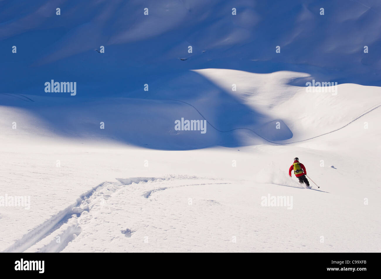 Austria, Zuers, Young man doing telemark skiing on Arlberg mountain - Stock Image