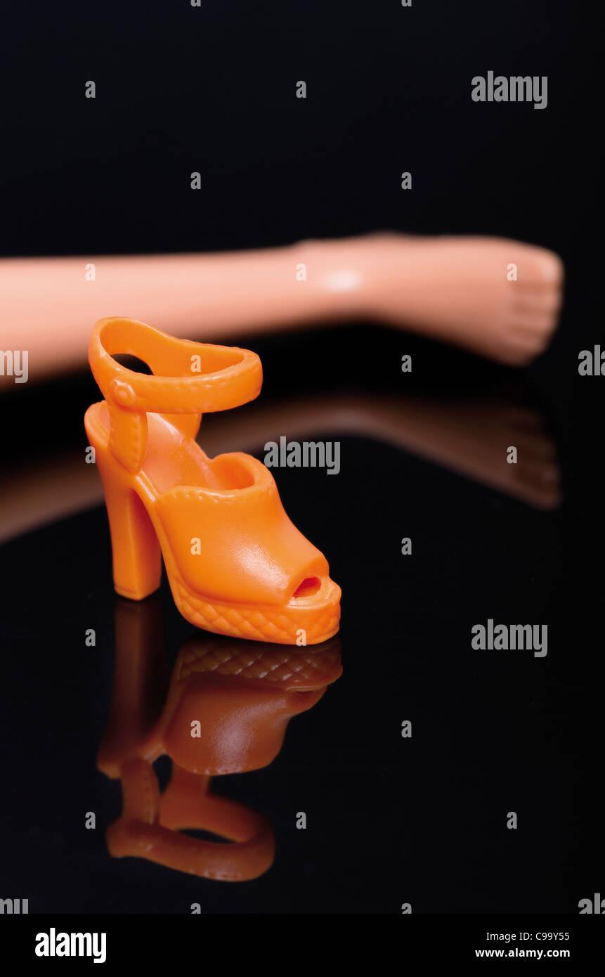 Doll feet besides high heels on black background Stock Photo