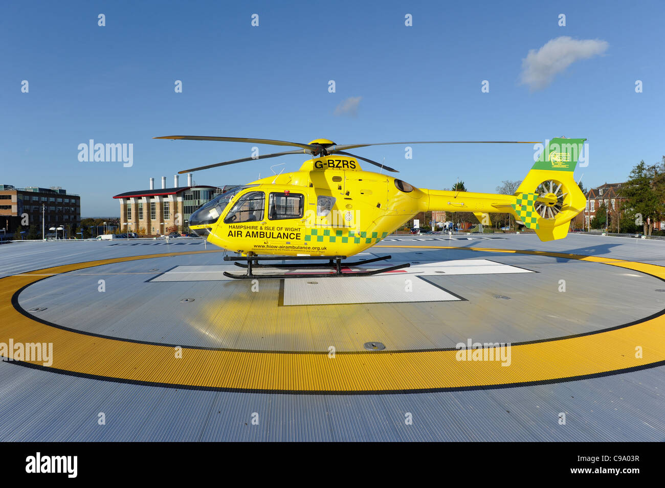 air ambulance of the hampshire and isle of wight sit on the helicopter landing pad of the southampton general hospital - Stock Image