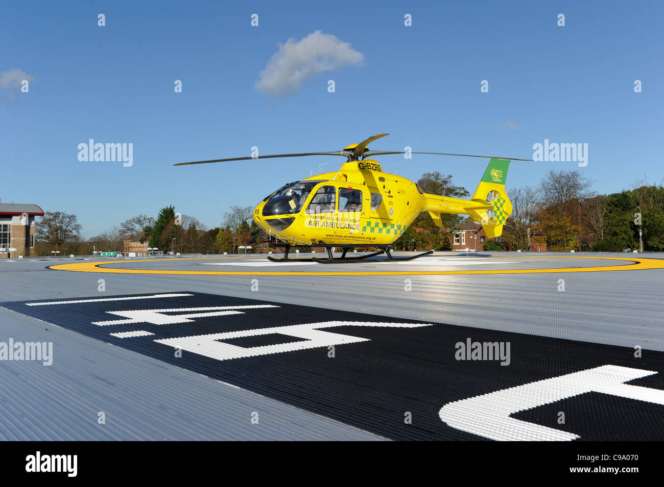 Southampton General hospital helicopter pad with a yellow air ambulance sitting on it - Stock Image