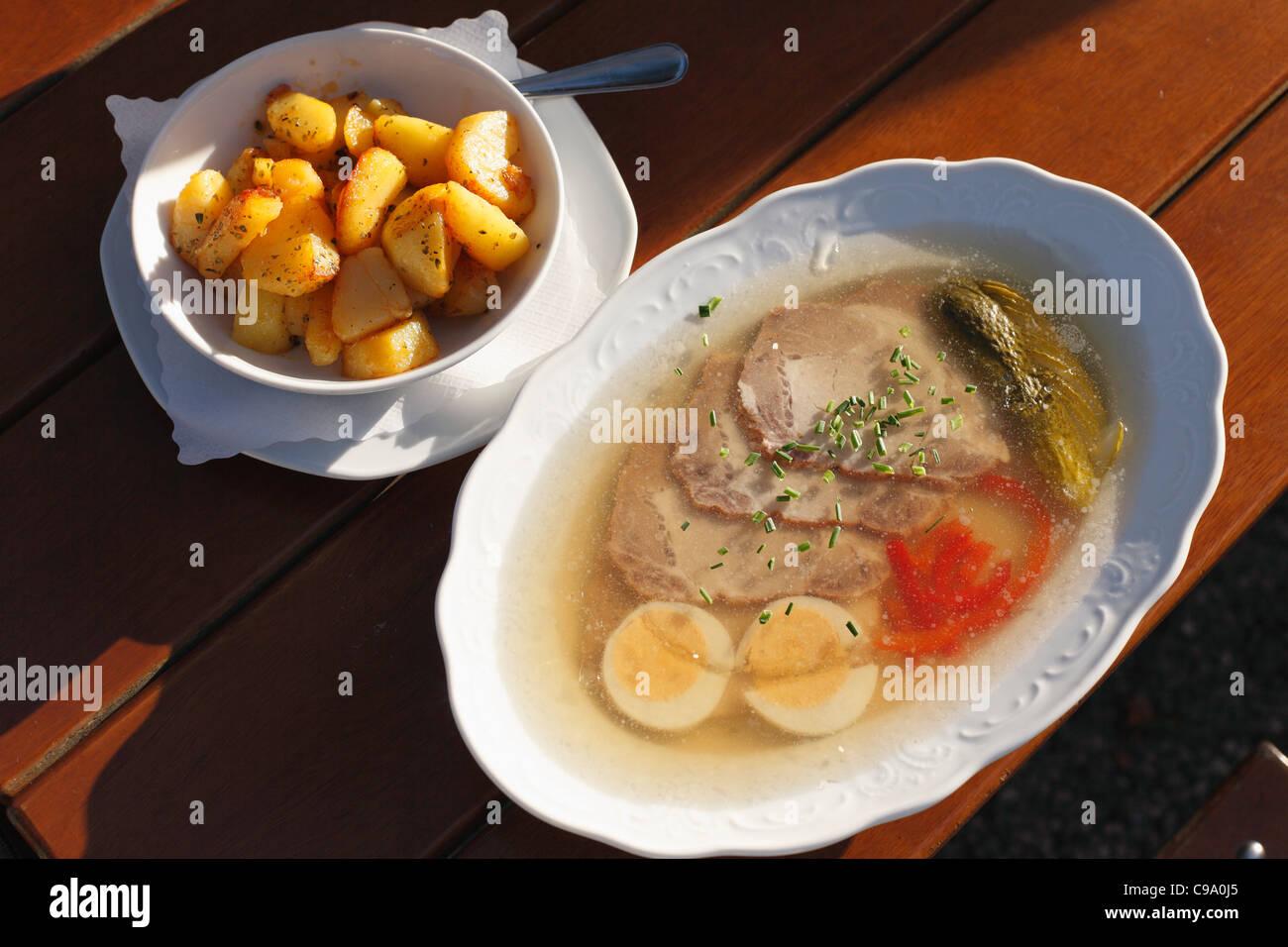 Germany, Bavaria, Murnau, Close up of roast aspic and fried potatoes on wood table - Stock Image
