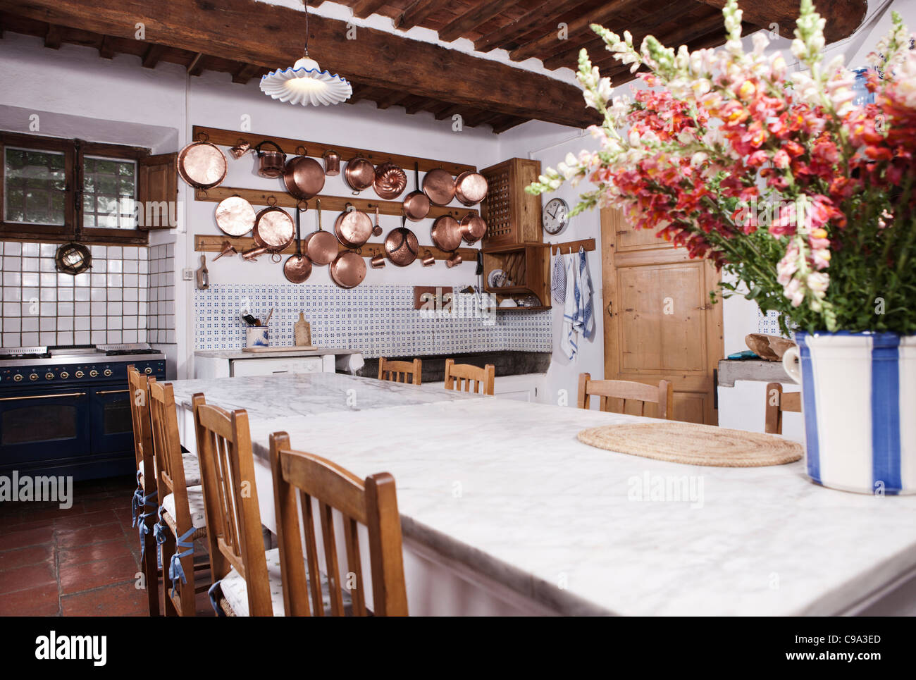 Italy, Tuscany, Magliano, View of kitchen with flowers on dining table - Stock Image