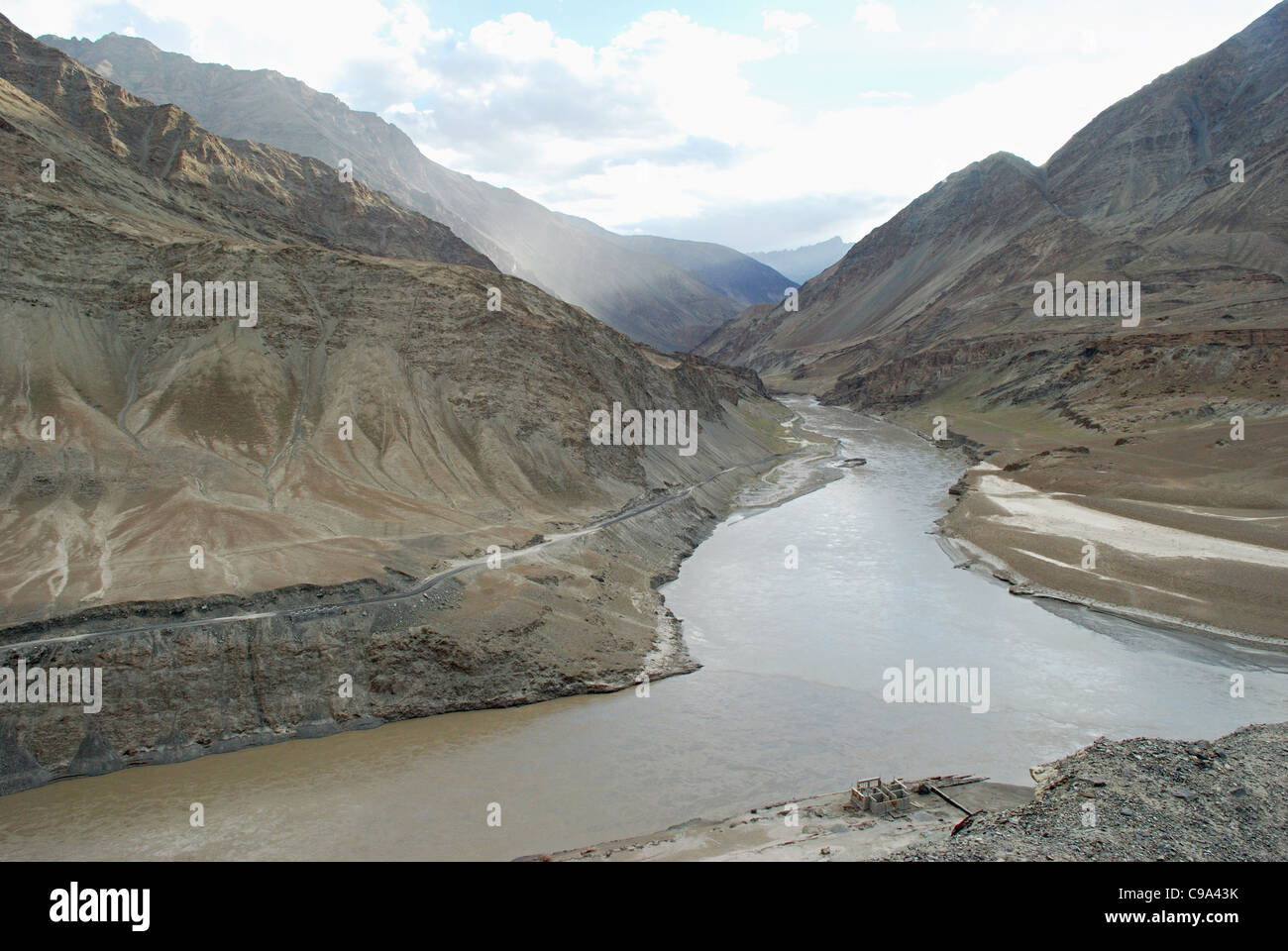 River Indus, near the confluence with river Zanskar against backdrop of the setting Sun – creating a spectrum of - Stock Image