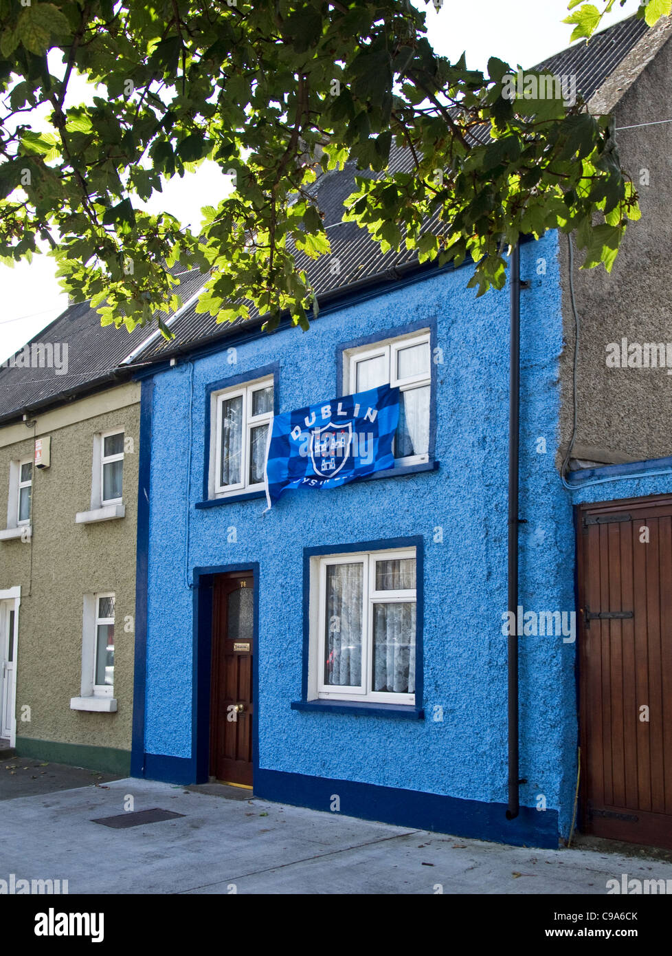 A small house decorated in the colours of the Dublin Gaelic football team with it's flag- Skerries, county Dublin, - Stock Image