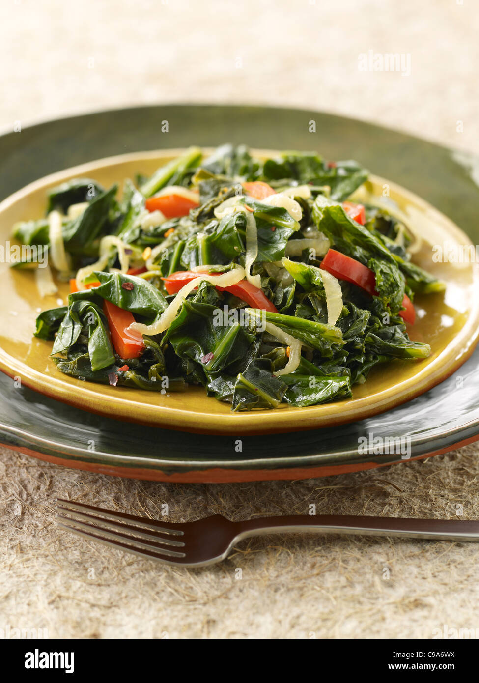 Sauteed leafy greens with onion and red bell peppers, - Stock Image