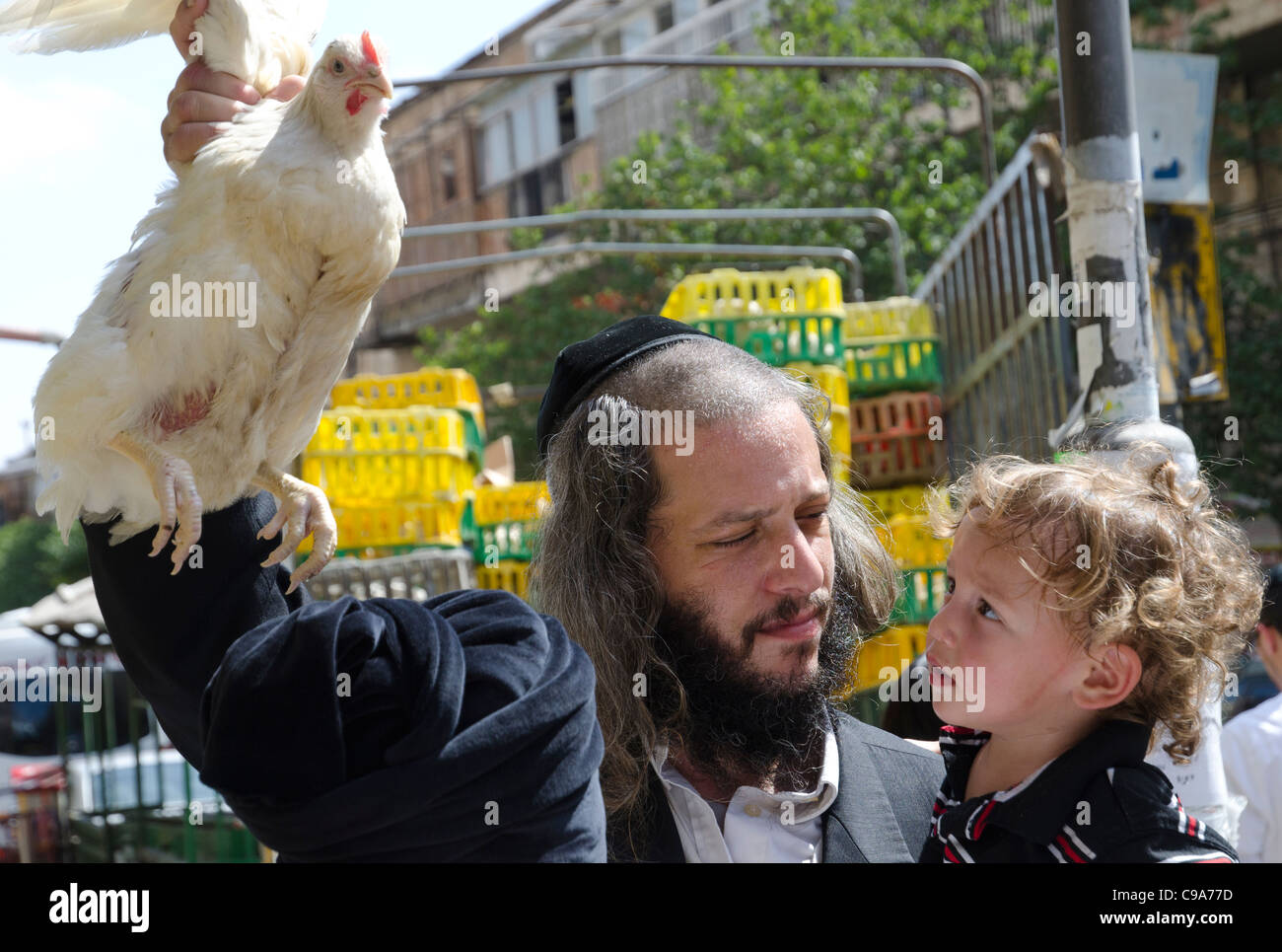 Orthodox jew with toddler performing the Kapparot ritual with a chicken. Mea shearim neighbourghood. Jerusalem - Stock Image