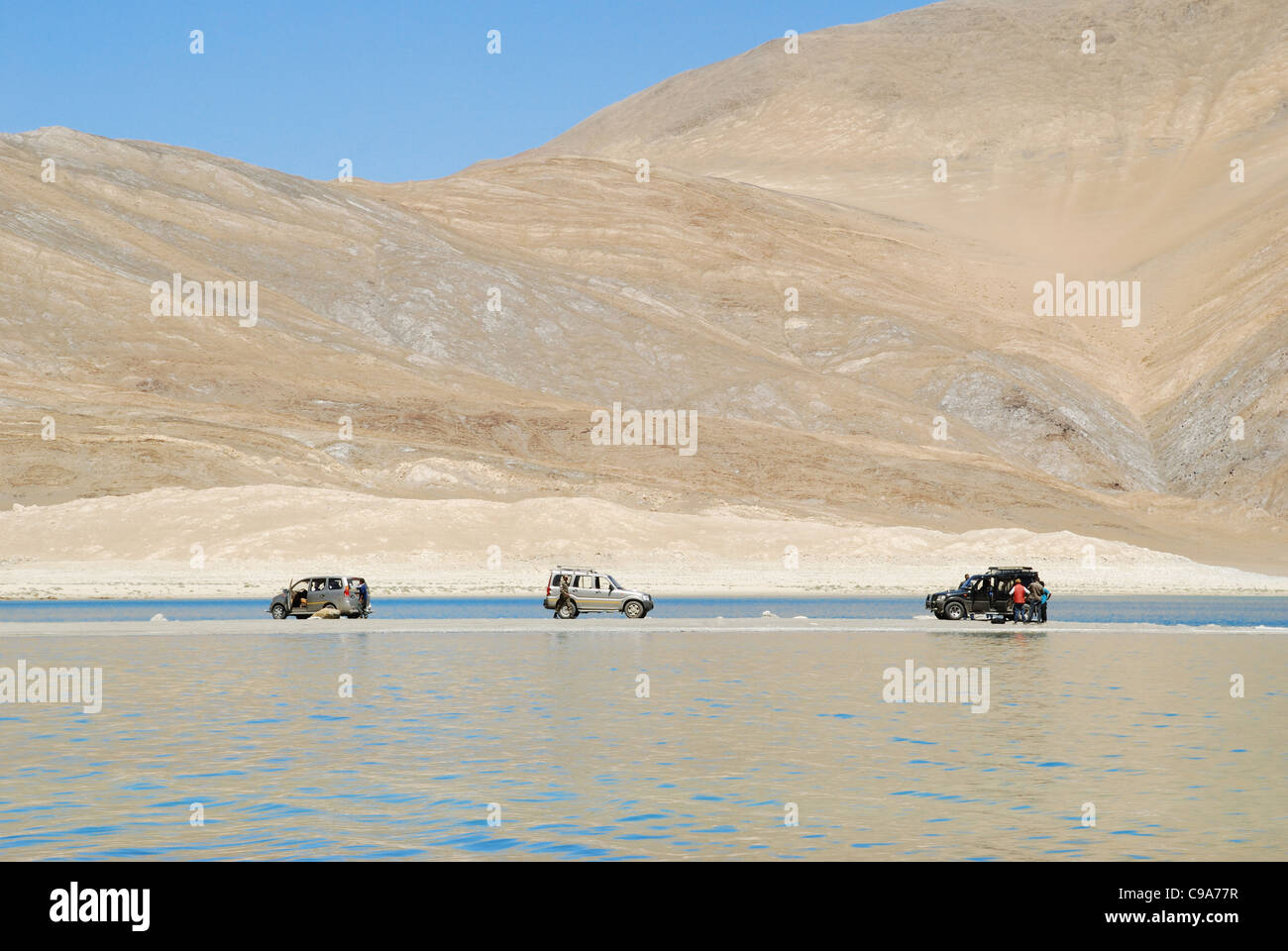 Three SUVs on an eye land in Pengong tso Lake ( an endorheic lake in the , situated at a height of about 4,350m Stock Photo