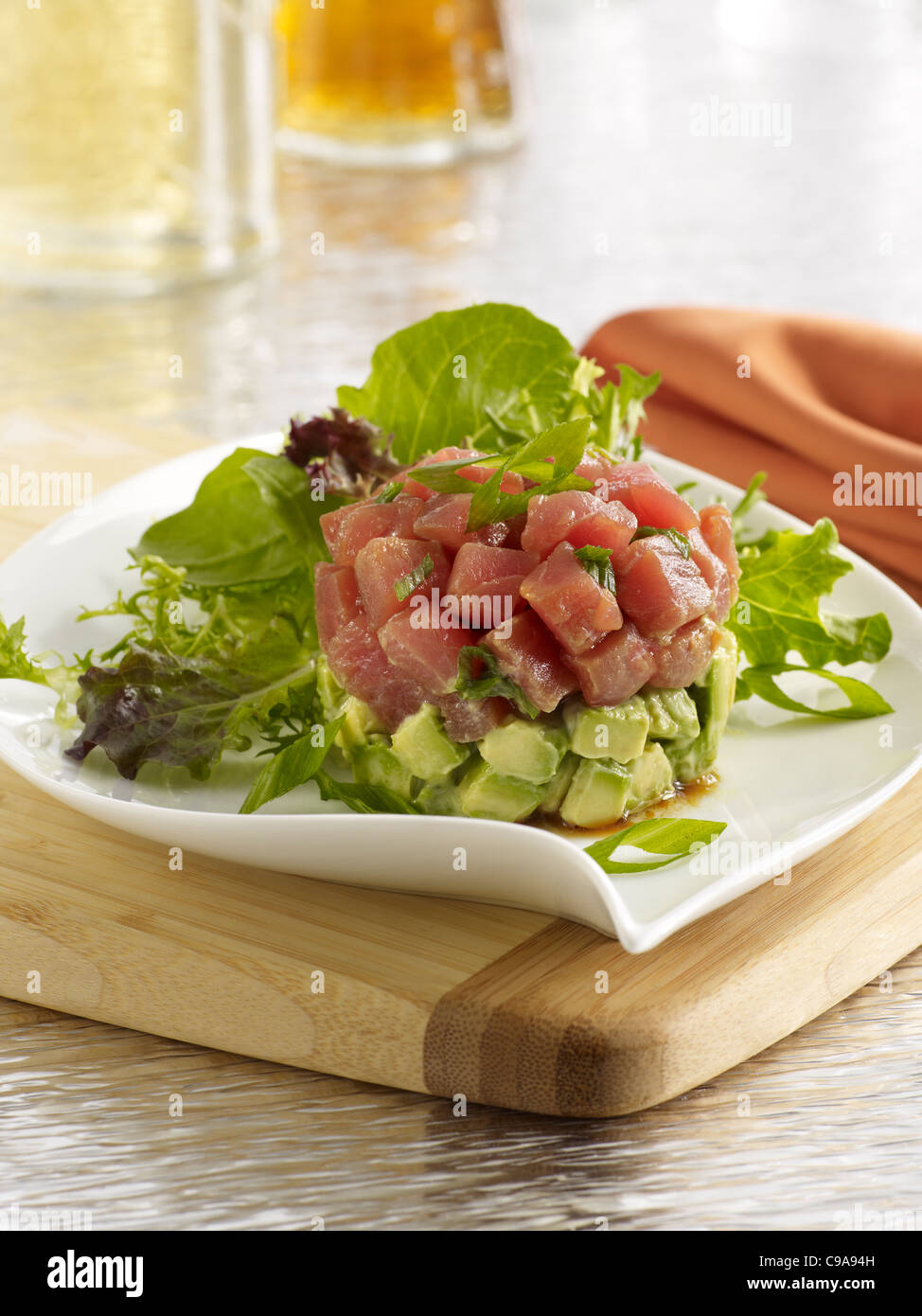 Tuna tartare salad with leafy greens and avocado on a white plate - Stock Image