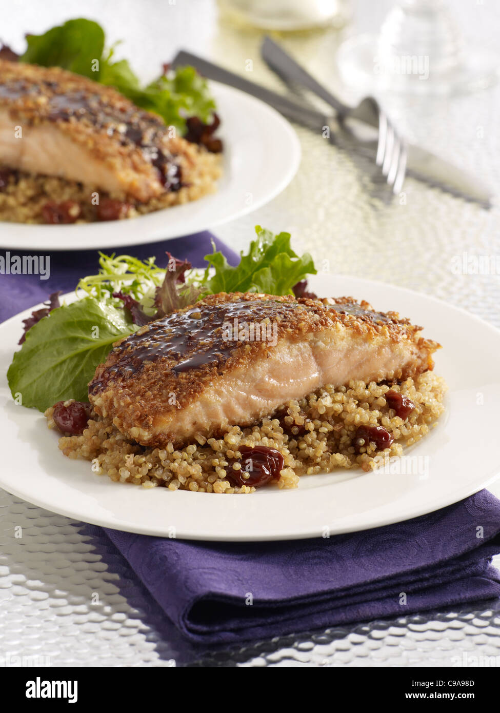 Cherry salmon fillet dinner over grains served with a leafy green salad - Stock Image