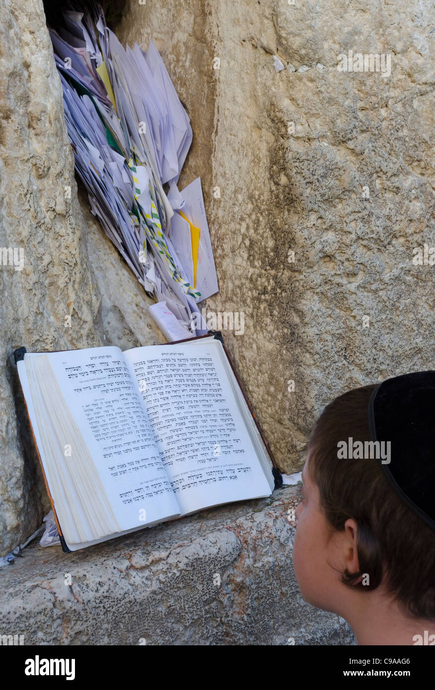 Young boy praying with paper notes in bkgd. Western Wall. israel - Stock Image