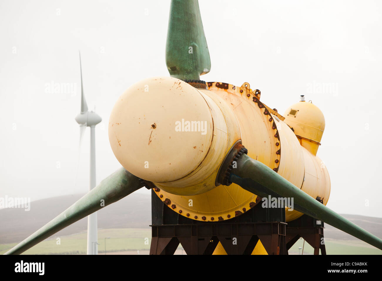 A tidal energy turbine on the dockside in Kirkwall, Orkney, Scotland, UK, with a wind turbine in the background. - Stock Image