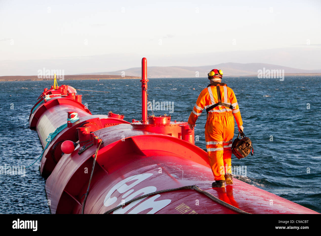 A Pelamis P2 wave energy generator on the dockside at Lyness on Hoy, Orkney Isles, Scotland, UK. - Stock Image