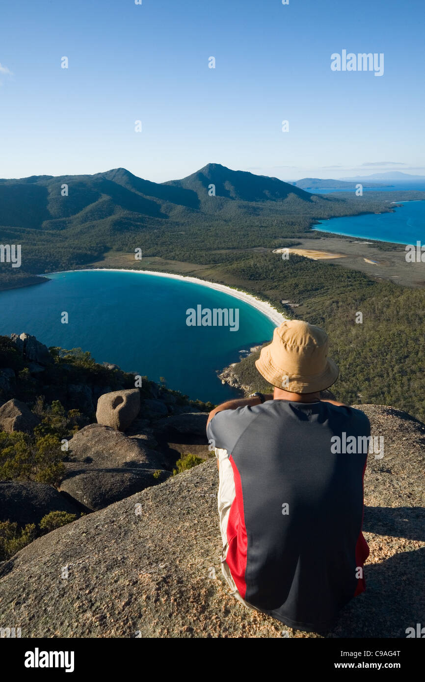 A man looks out over Wineglass Bay from the summit of Mt Amos.  Freycinet National Park, Tasmania, Australia - Stock Image