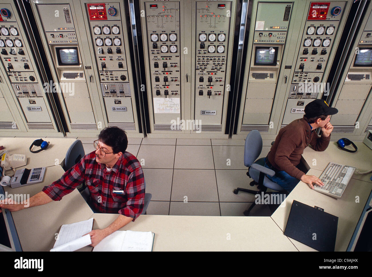 Control room workers at a gas turbine co-generation plant (natural gas to electric) - Stock Image