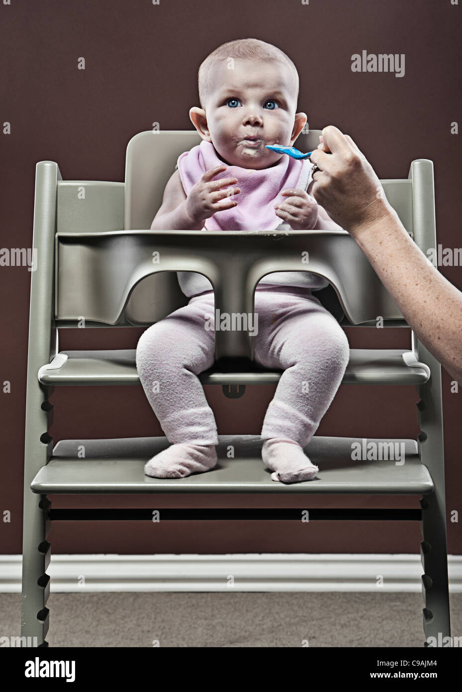 Four month old Baby Girl Eating First Food in Highchair - Stock Image