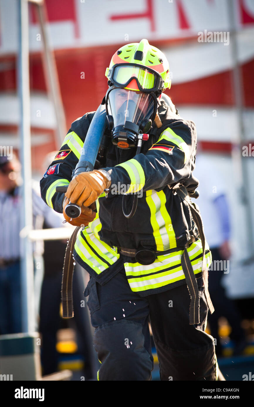 A firefighter races with a firehose while wearing full firefighting gear and working against the clock during the - Stock Image