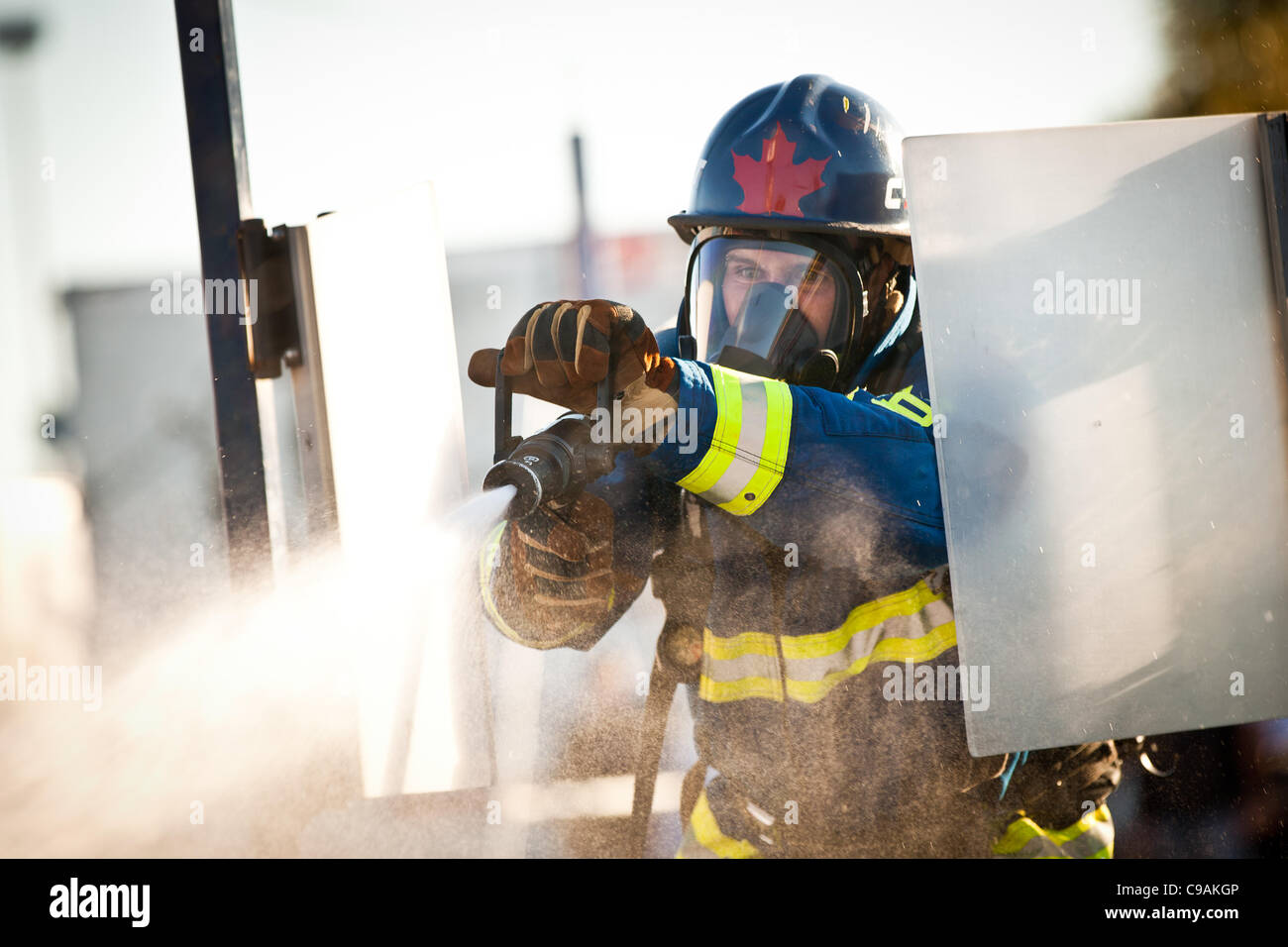 A firefighter from Canada aims a firehose at a target while wearing full firefighting gear and working against the - Stock Image