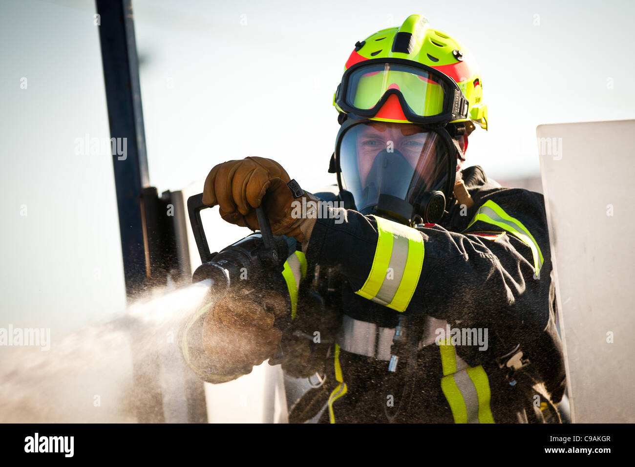 A firefighter aims a firehose at a target while wearing full firefighting gear and working against the clock during - Stock Image