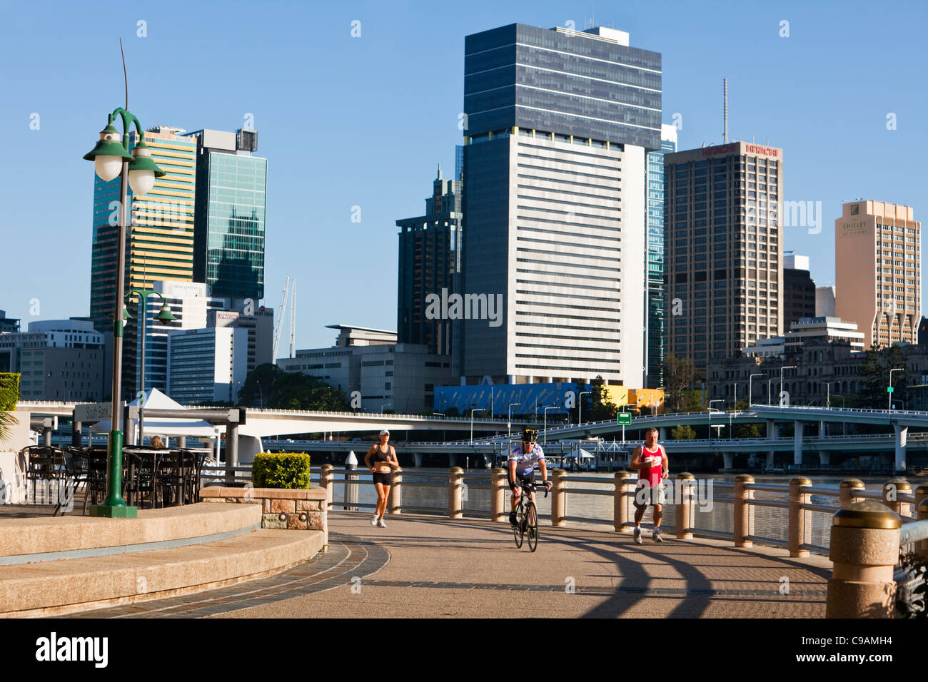 Early morning cyclists and joggers at South Bank Parklands with city skyline in background.  Brisbane, Queensland, - Stock Image