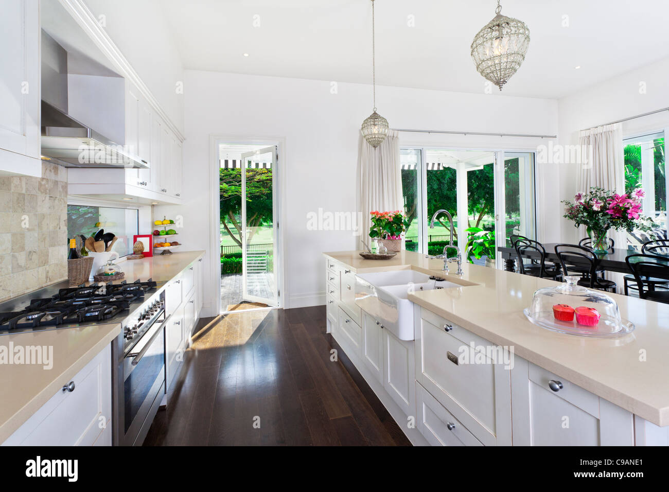 Stylish open plan kitchen with stainless steel appliances and dining ...