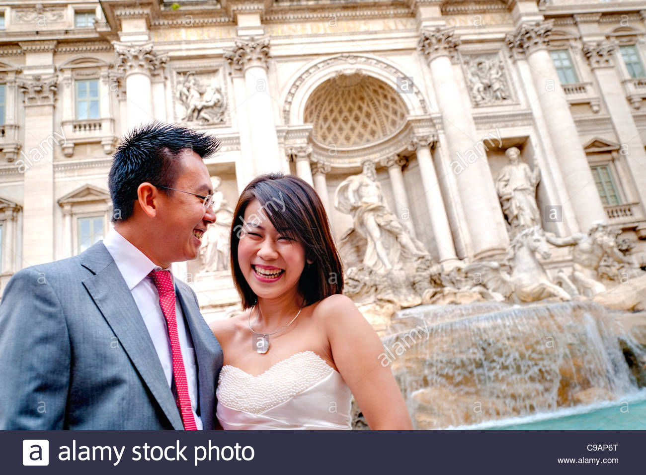 Newlyweds laughing in front of Fontana di Trevi - Stock Image