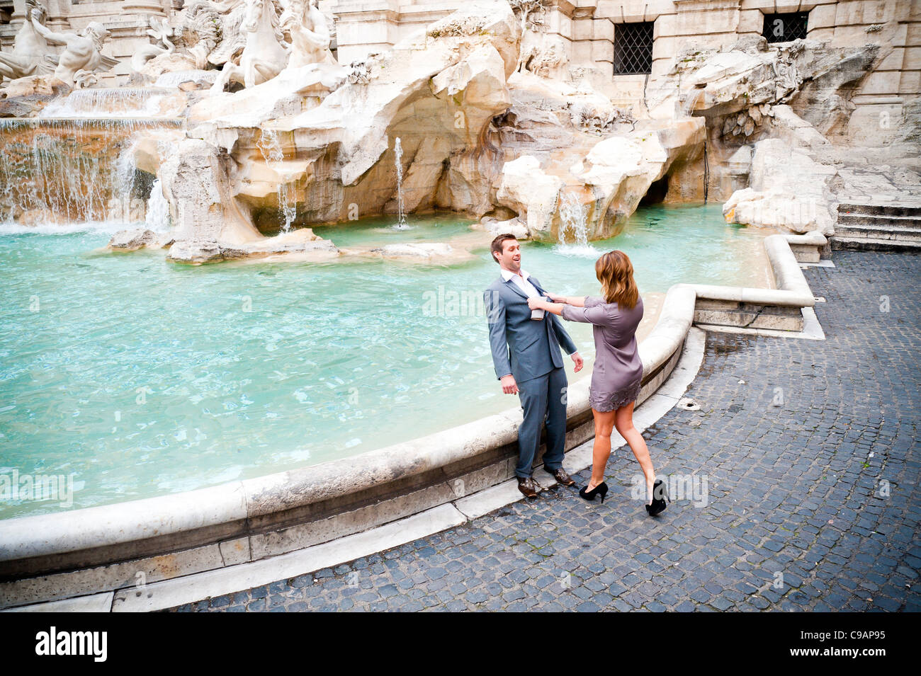 Woman pushing man into the Trevi fountain as a joke - Stock Image