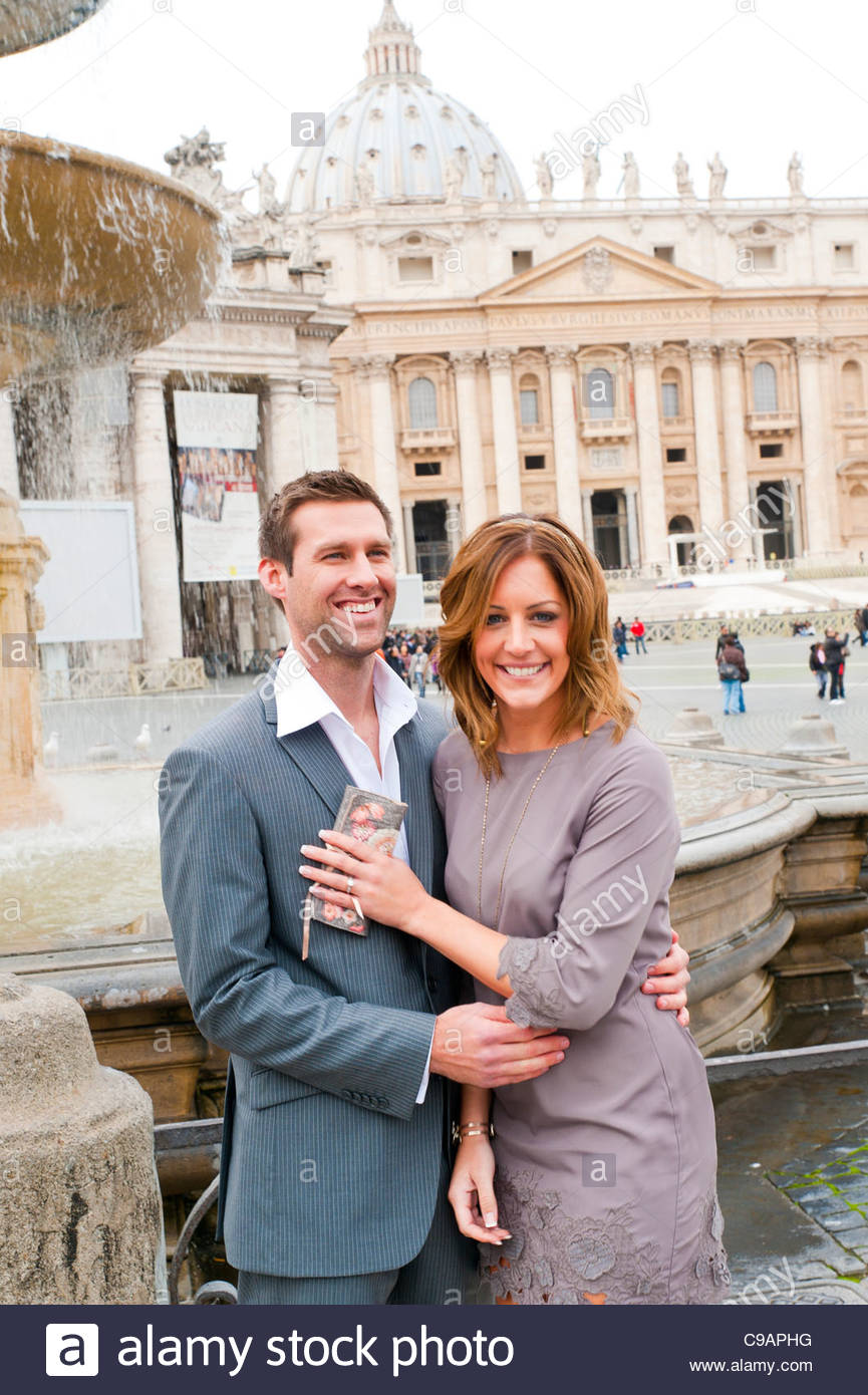 Couple standing in front of a water fountain in Saint Peter's square - Stock Image