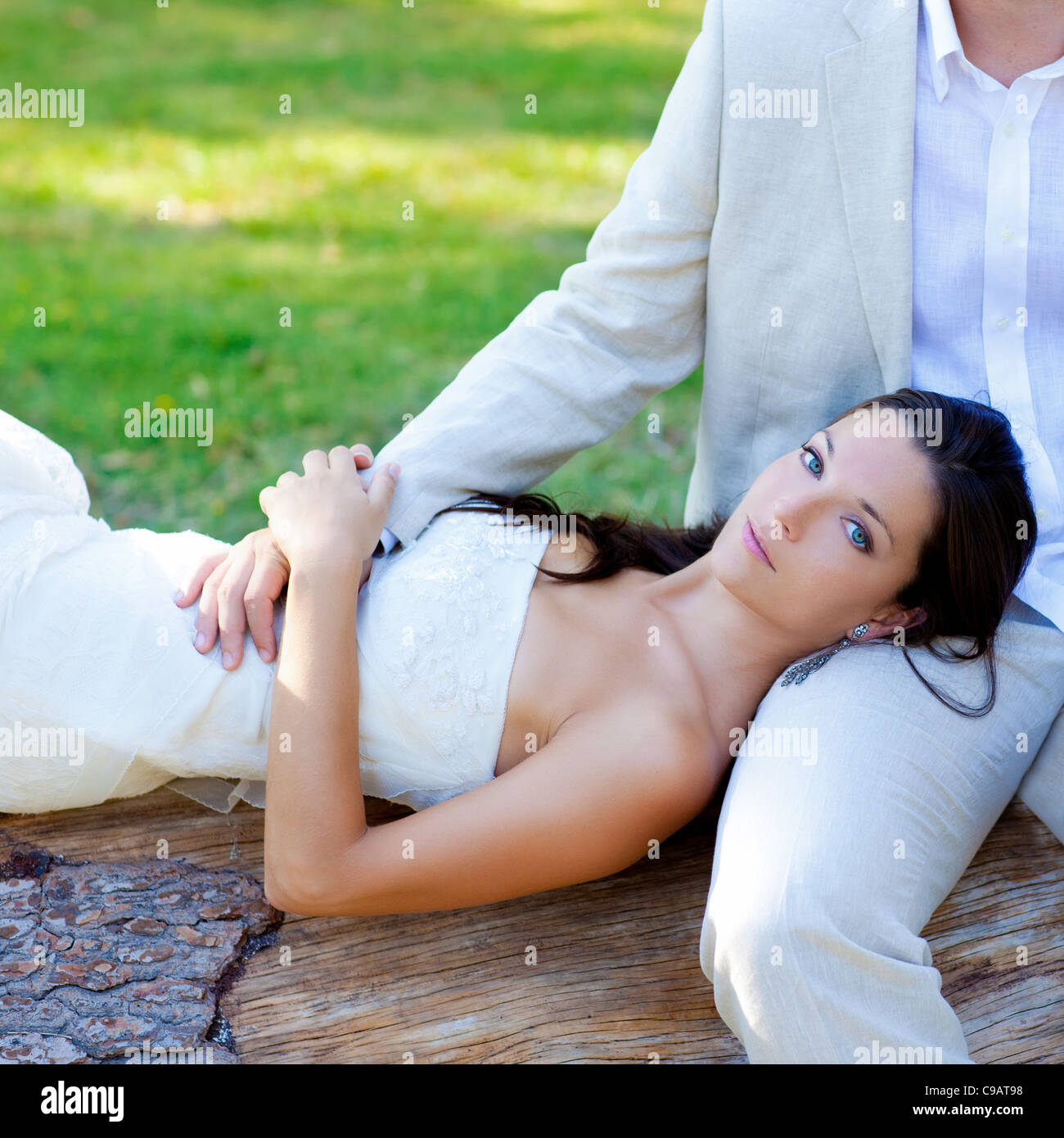 woman lying on husband leg in a park trunk just married - Stock Image