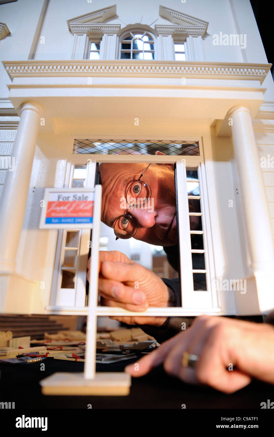 A miniatura enthusiast places a for sale outside his regency mansion dolls' house at the miniature modelling - Stock Image