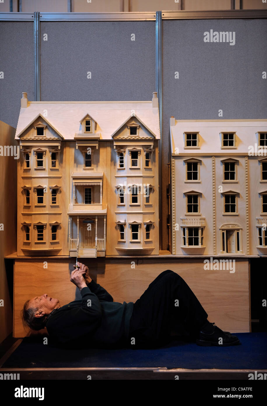A miniatura enthusiast working on his Pennsylvanian style villa dolls' house at the miniature modelling Show at Stock Photo